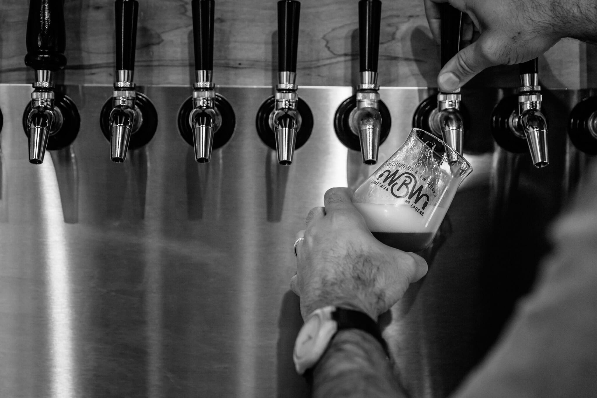 A picture of beer taps and someone pouring a fresh beer